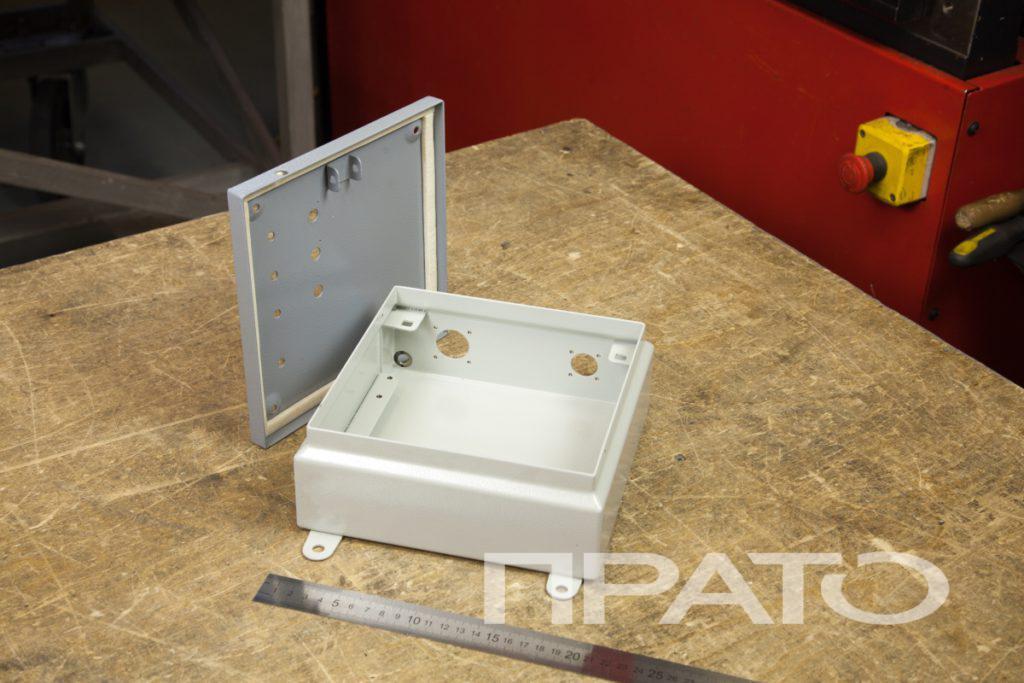 Ящик IP54. Металлообработка ПРАТО, Сергиев Посад, квадратная форма, железная линейка, крышка с перфорацией, деревянный стол, красная панель аппарата на фоне, желтая кнопка, деталь, круглые отверстия, производство, изделия из металла, цех