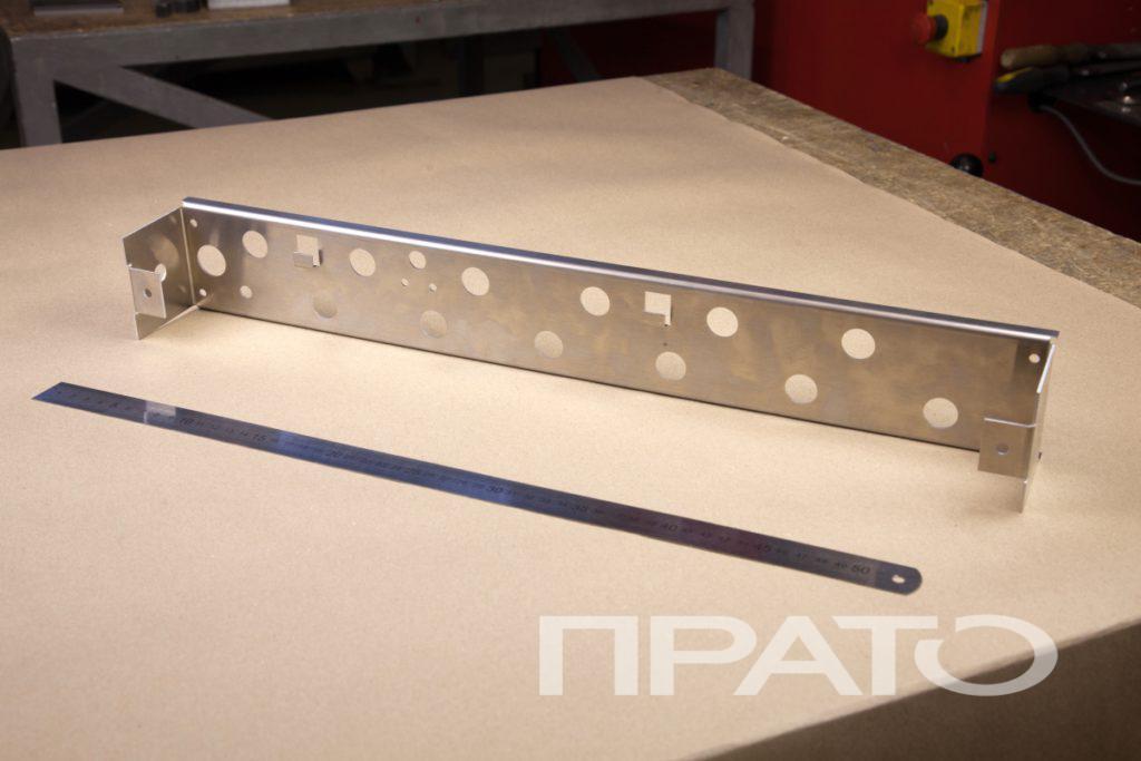 Панель с отверстиями. Металлообработка ПРАТО, Сергиев Посад, круглые отверстия, продолговатая панель, прямоугольная деталь, продукция из металла, длинное изделие, железная линейка, деревянный стол, производство, цех