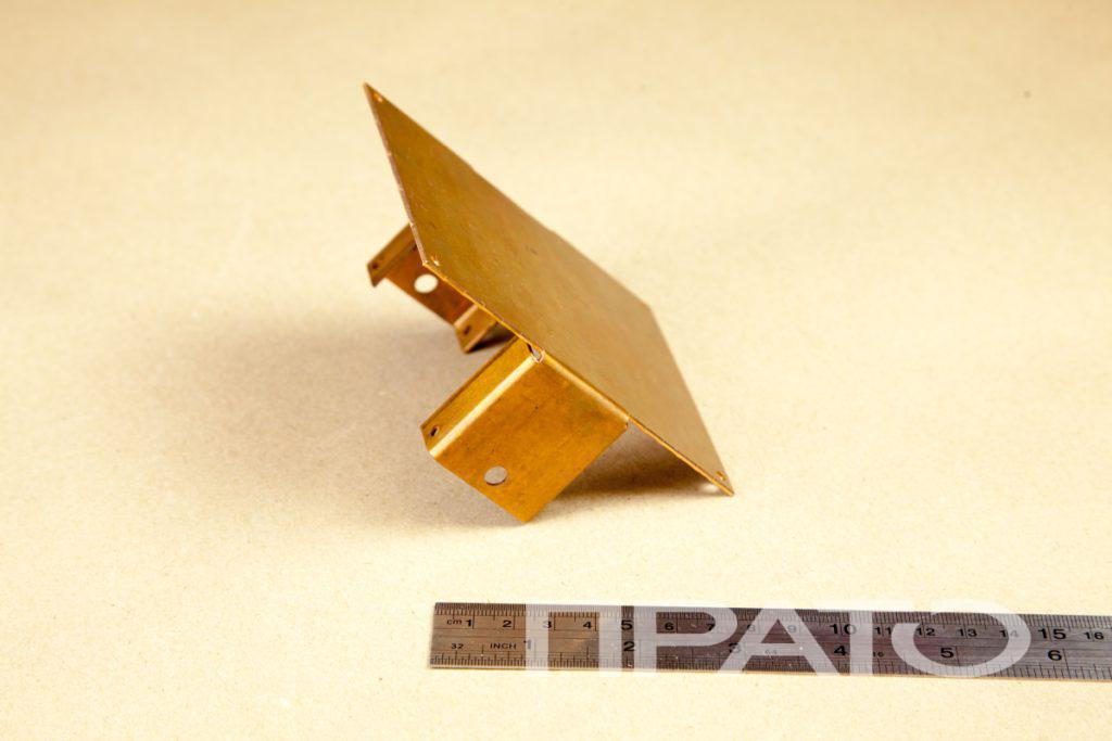 Основание. Металлообработка ПРАТО, Сергиев Посад, комплектующие, изделие, металл, деталь, золотой цвет, круглые прорези, отверстия, гибка, плоская квадратная панель, деревянный стол, железная линейка, производство, цех