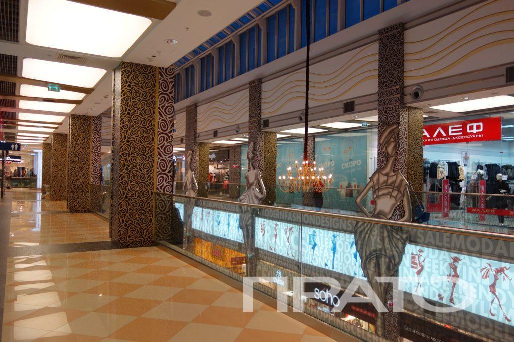Пешеходная зона – вид 1. ТРЦ Июнь, г. Мытищи. Светотехника ПРАТО, Сергиев Посад, расписные прямоугольные колонны, квадратные светильники, лампа, люстра, свет, освещение, подсветка, фигуры, женщины, торговый центр, стеклянные ограждения, перила, магазины, пол в клетку, объект, проект