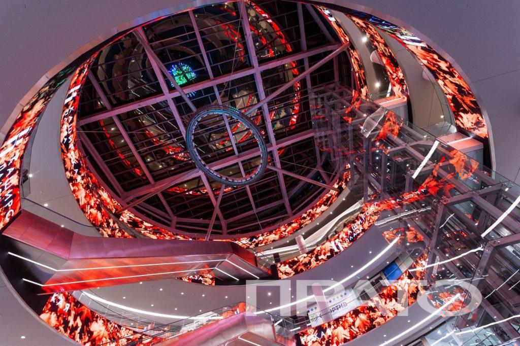 Пешеходная зона – вид 3. ТЦ Каширская Плаза, г. Москва. Светотехника ПРАТО, Сергиев Посад, стеклянный потолок, архитектура, дизайн, эскалатор, лава, красные тона, освещение, свет, подсветка, лампа, люстра, отражение, стеклянный лифт, светильник, объект, проект, торговый центр, магазин, шопинг