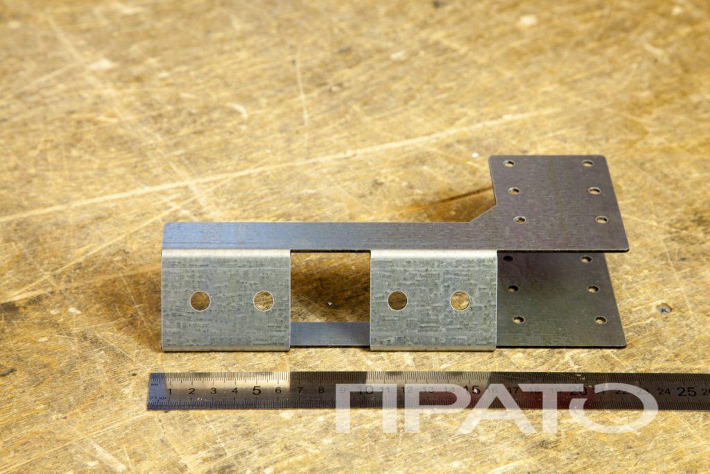 Кронштейн крепления балки. Металлообработка ПРАТО, Сергиев Посад, деталь для крепления, комплектующая, гибка металла, круглые отверстия, деталь, железная линейка, деревянная столешница, производство, цех