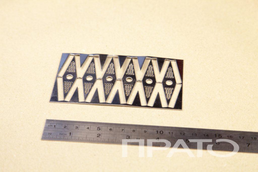 Кронштейн перфорированный. Металлообработка ПРАТО, Сергиев Посад, сложные прорези, прямоугольная форма, орнамент, симметрия, круглые и продолговатые отверстия, железная линейка, деревянный стол, изделия, металл, деталь, производство, цех